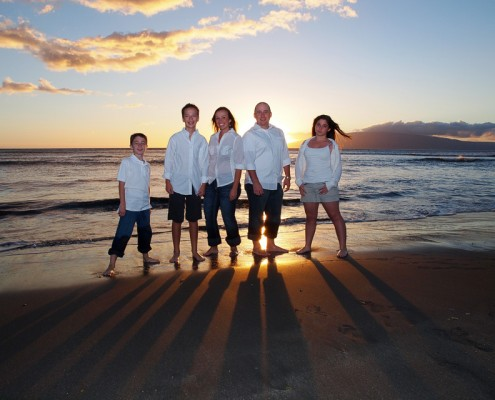 picture of family at sunset on Maui beach with striking colors in the sky