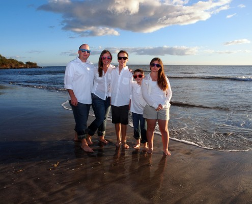 family wearing sunglasses on maui beach at sunset
