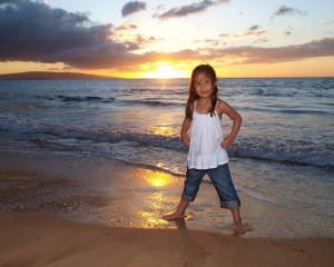 young girl standing on the beach at sunset