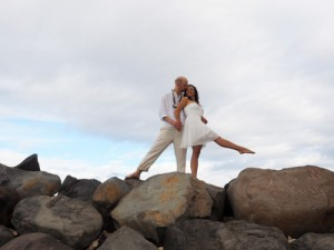 a couple pose stringly while on a mass of boulders