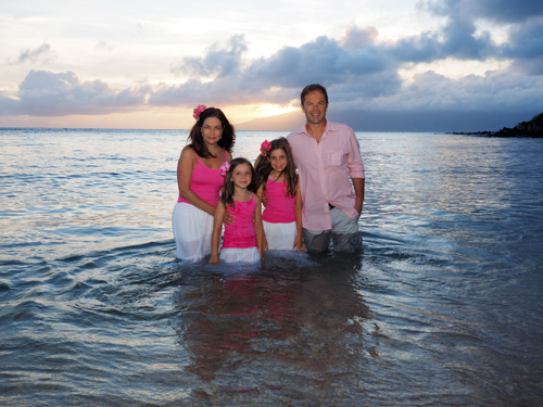 a family of four pose for portraits in the water at Kapalua Bay, Maui, Hawaii