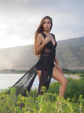 Young beautiful model posing in a flowing black dress near the beach