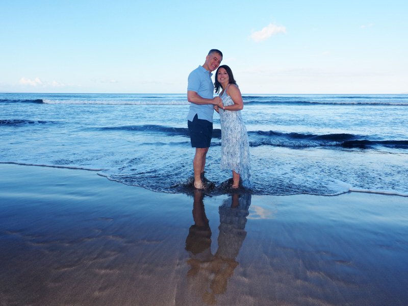 A couple at the water line of a calm Maui beach