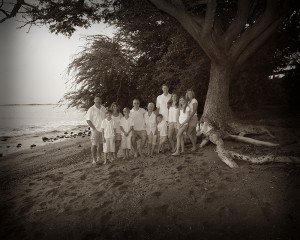A large family by a tree at the beach as an old time photograph