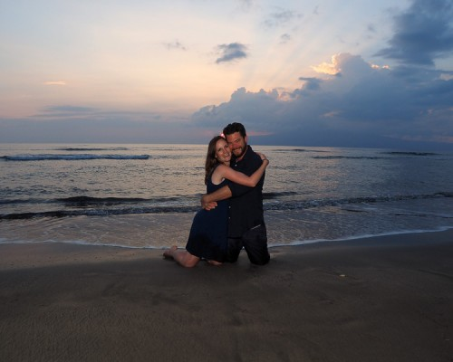 embracing couple on beach at sunset