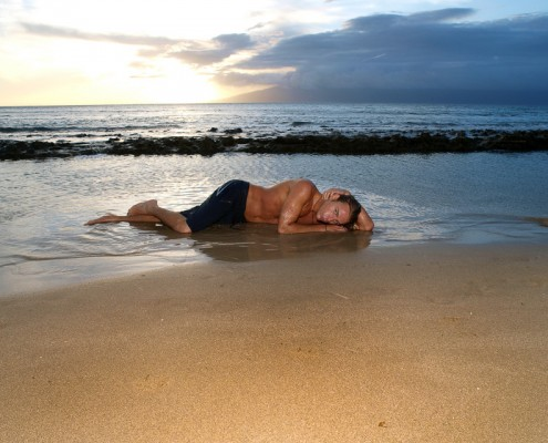 Male Model Laying on Beach at Sunset near Lahaina, Maui, Hawaii