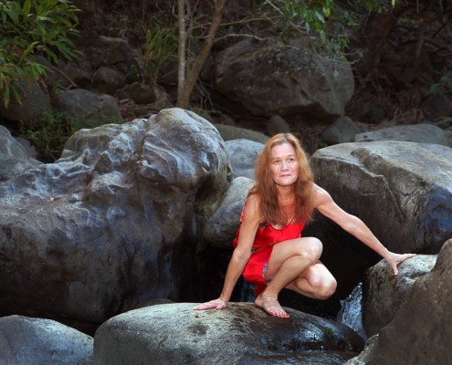 Iao Stream Portrait Photo of a woman in a red dress kneeling on rocks
