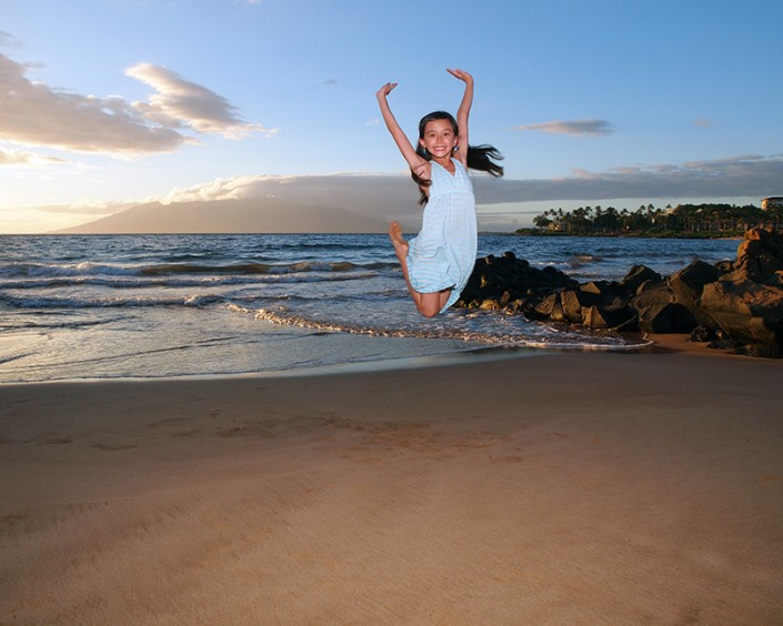 a happy fun loving child jumping on maui beach