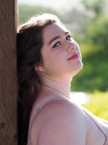 plus fun - headshot of plus size woman with sun as hairlight and backlight
