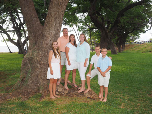 A family of 6 pose by one of the stately trees at Launiupoko Beach Park, Lahaina, Maui