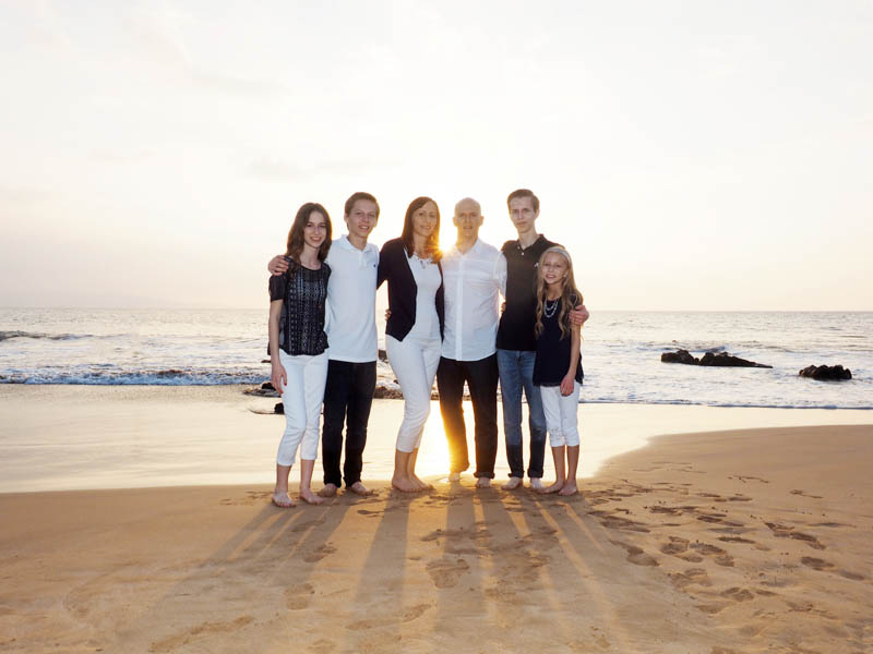 A family poses on a Maui beach backlit from the setting sun