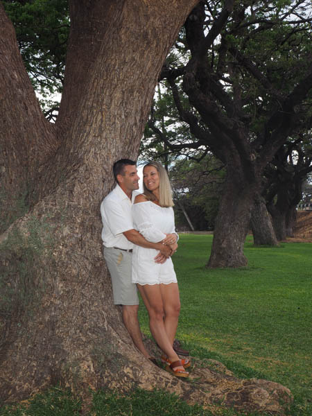 A loving couple by a tree in a park
